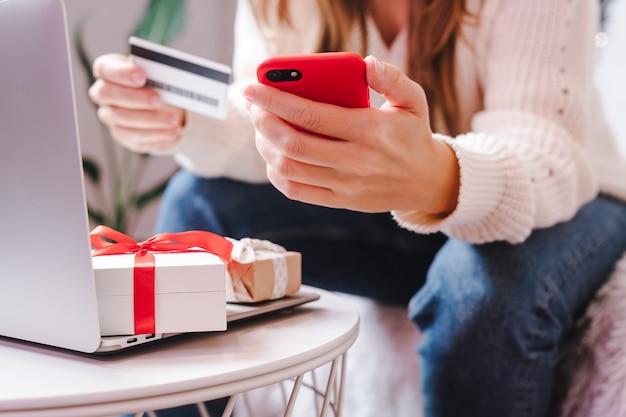 Закройте руки женщины с мобильным телефоном, кредитной картой, подарками и ноутбуком