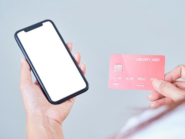 女性のクローズアップは、灰色の背景に携帯電話、空白の画面、クレジットバンクカードを保持します。