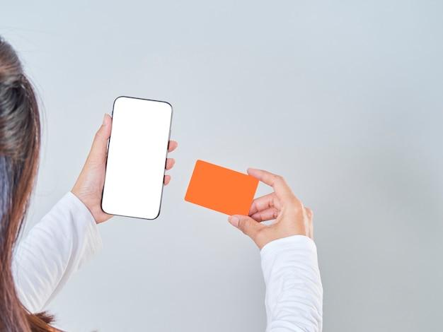 灰色の背景に女性のクローズアップを保持するスマートフォン、空白の画面、クレジットバンクカード