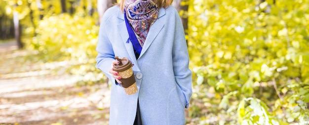 秋の風景のテイクアウトコーヒーカップを保持している女性のクローズアップ