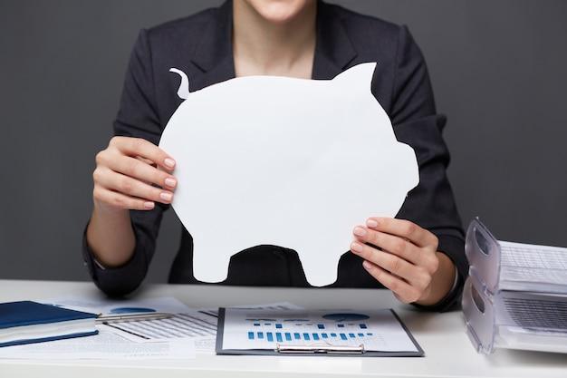 白の貯金箱を持った女性のクローズアップ