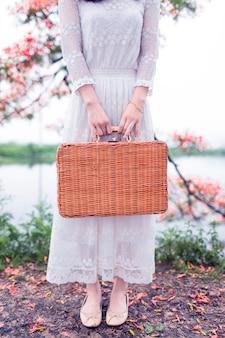 籐のブリーフケースを保持している女性のクローズアップ