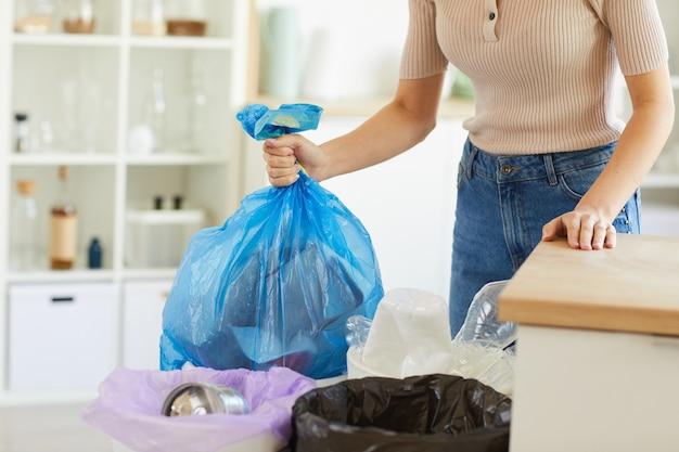 Крупный план женщины, держащей в руках большой мешок с мусором и выбрасывающей его в мусорное ведро
