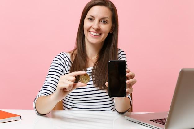 Крупным планом женщина, держащая биткойн металлическую монету золотого цвета, будущую валюту и мобильный телефон с пустым пустым экраном, сидит за столом