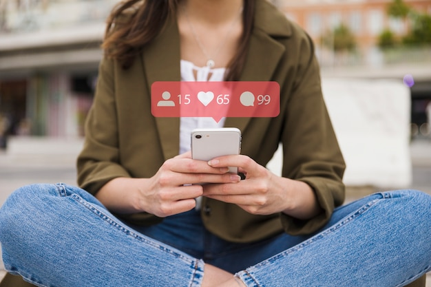 携帯電話、ソーシャルメディアネットワークアイコンを持つ女性のクローズアップ