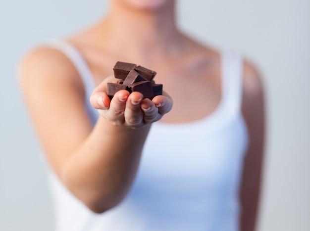 チョコレート、チョコレートフォーカスを持つ女性のクローズアップ