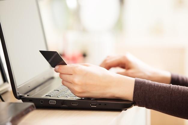 Крупный план женщины, держащей кредитную карту и использующей ноутбук