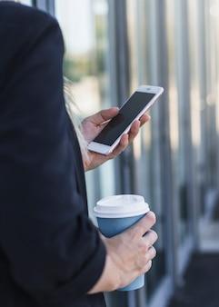 휴대 전화를 사용하여 일회용 커피 컵을 들고 여자의 근접 촬영
