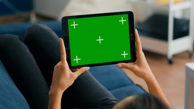 소파에 누워 있는 모의 녹색 화면 크로마 키 디스플레이가 있는 수평 모드 태블릿 컴퓨터를 들고 있는 여성의 클로즈업. 소셜 네트워크 탐색을 위해 격리된 터치스크린 장치를 사용하는 프리랜서