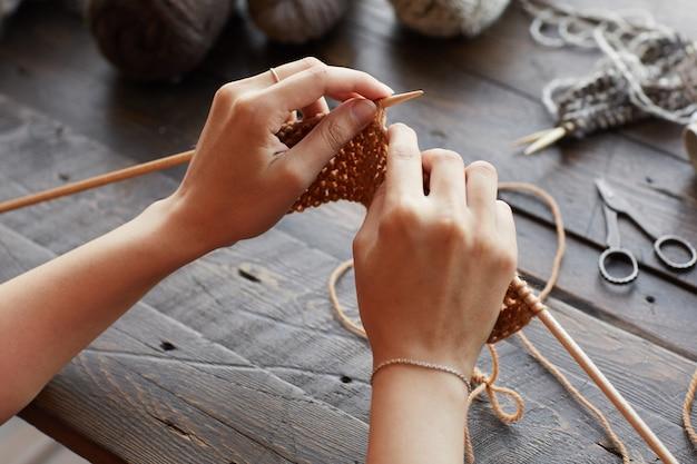 編み針を持って、ウールから暖かい服を編む女性のクローズアップ