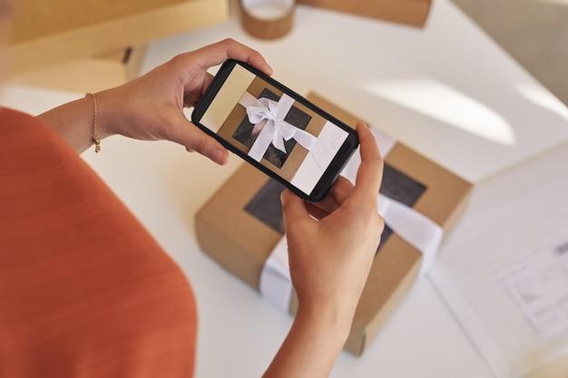 携帯電話を持って、テーブルに飾られた小包の写真を作る女性のクローズアップ