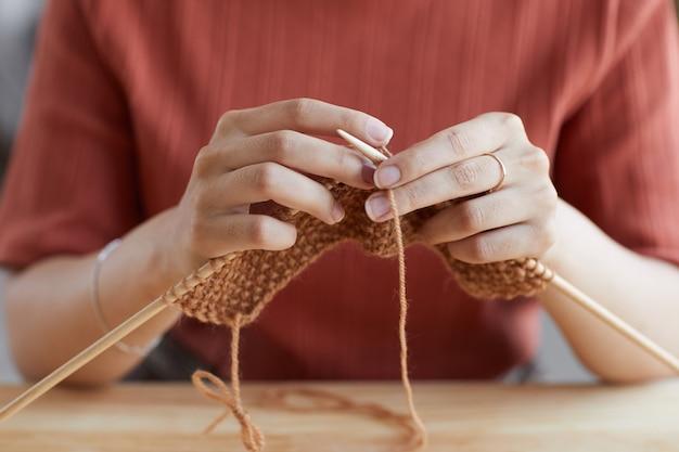 彼女はウールからセーターを編んで針を持っている女性のクローズアップ