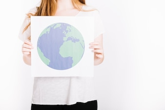 Close-up of woman holding paper with printed globe against white background