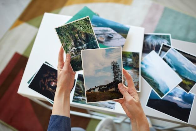 Крупный план женщины, держащей фотографии в руках, вспоминая свои лучшие моменты