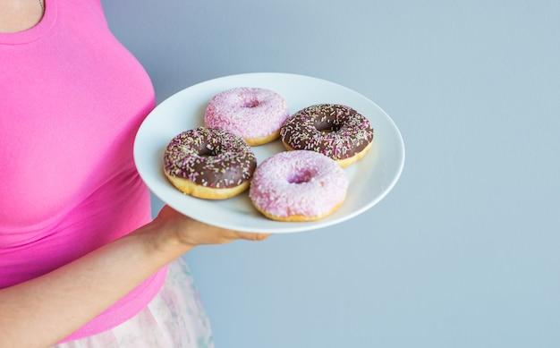 맛 있는 달콤한 도넛과 함께 접시를 들고 여자의 클로즈업.