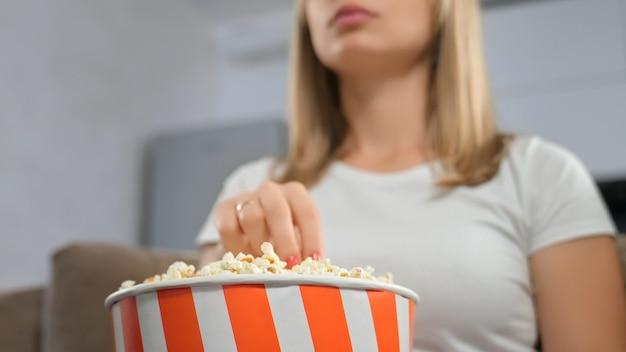 Закройте вверх женщины, держащей коробку попкорна.