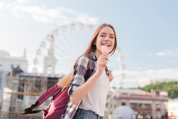 Крупным планом женщина, держащая мороженое эскимо и улыбается