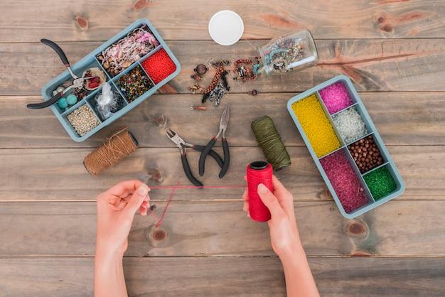 木製の机の上の創造的なビーズの手作り材料と赤い糸のスプールを保持している女性のクローズアップ