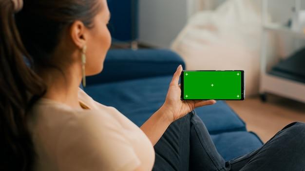 거실 소파에 앉아 있는 동안 모의 녹색 화면 크로마 키 디스플레이가 있는 스마트폰을 들고 있는 여성의 클로즈업. 소셜 네트워크 탐색을 위해 격리된 터치스크린 장치를 사용하는 프리랜서