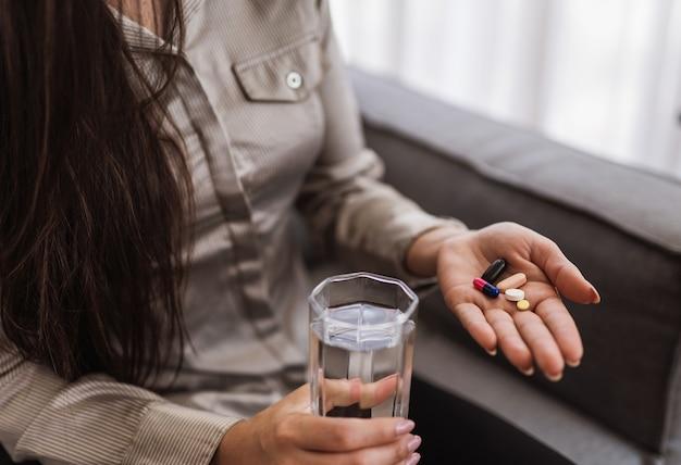 다양한 정제, 알약, 물 한 잔을 들고 있는 여성의 클로즈업.