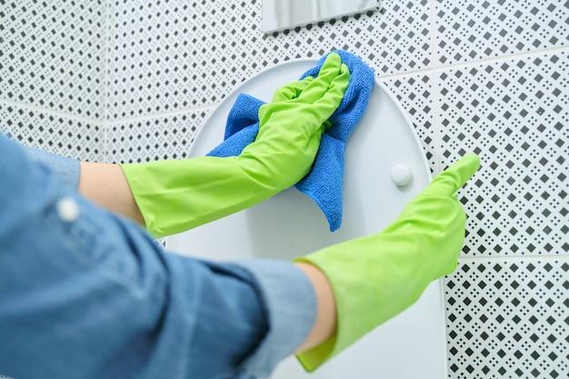 ぼろきれと洗剤洗浄便器、バスルームでの家の掃除と手袋をはめた女性のクローズアップ