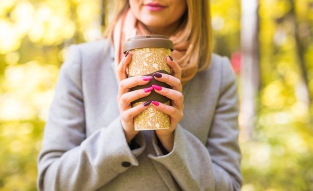 커피 한 잔을 들고 회색 코트에 여자의 클로즈업