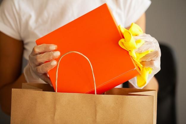 ショッピングを消毒する保護手袋を着用した女性のクローズアップ。