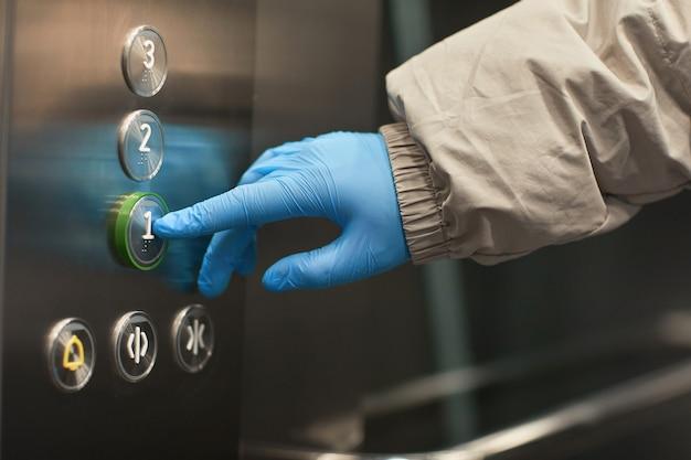 엘리베이터에서 버튼을 누르면 보호 장갑에 여자의 근접