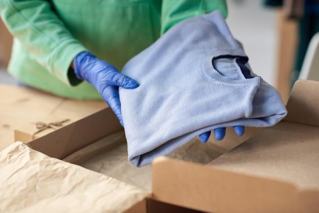 段ボール箱に新しい服を詰めて小包を作る保護マスクの女性のクローズアップ