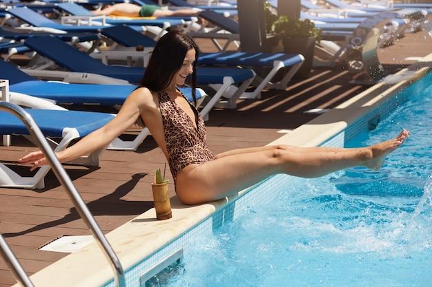 ヒョウ柄のスイミングプールの端に座っている水着の女性のクローズアップ、手を広げ、足を上げて、彼女の近くのカクテルでポーズします。リゾートで夏の日を過ごして過ごす女性。