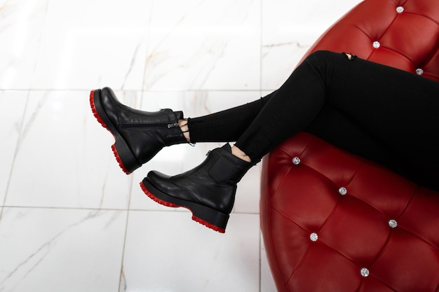 赤い靴底の流行の春秋革靴の女性のクローズアップ