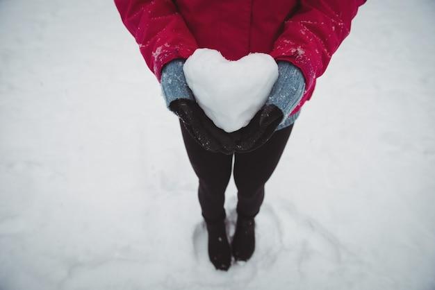 雪の心を保持している暖かい服を着た女性のクローズアップ