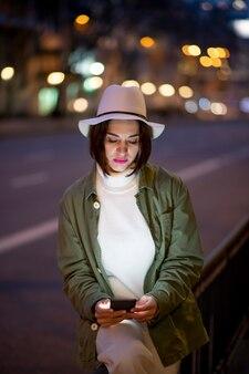 通りを歩きながらスマートフォンを使用して白い帽子をかぶった女性のクローズアップ