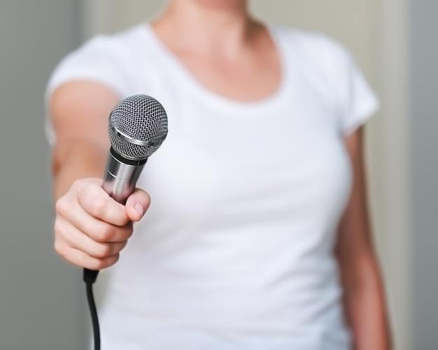 Крупным планом женщина в белой рубашке, которая предлагает кому-то дать ей интервью. держа микрофон в руке.