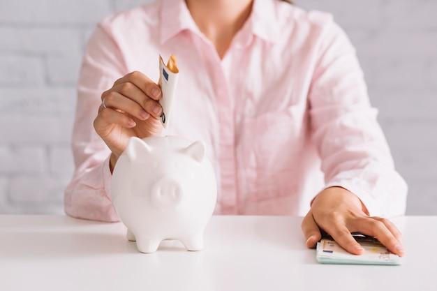 白いpiggybankでユーロを挿入している女性のクローズアップ