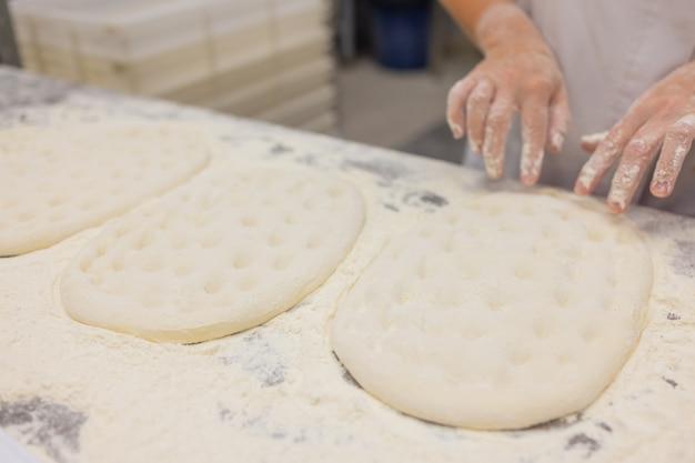 ピザ生地をこねる女性のクローズアップ。