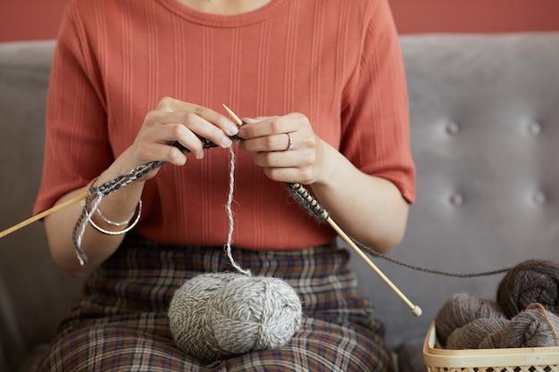 ソファに座って自分のために暖かいウールのスカーフを編んでいる女性のクローズアップ