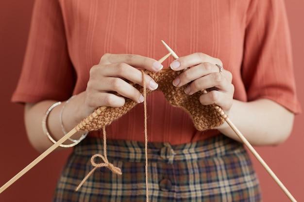 ピンクの壁に立っている糸からスカーフを編む女性のクローズアップ