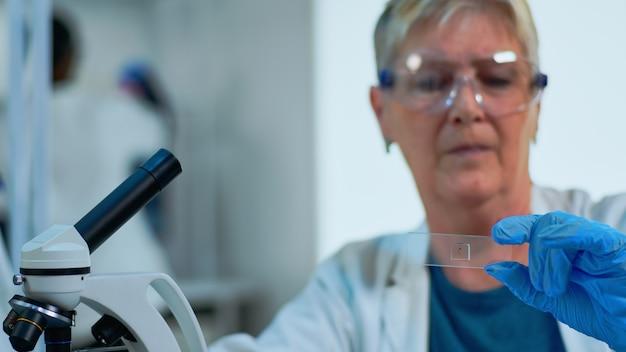 현대적인 시설을 갖춘 실험실에서 바이러스 샘플을 분석하는 여성 실험실 엔지니어의 클로즈업. 다양한 박테리아, 조직 및 혈액 검사와 함께 일하는 수석 의사, 항생제에 대한 제약 연구