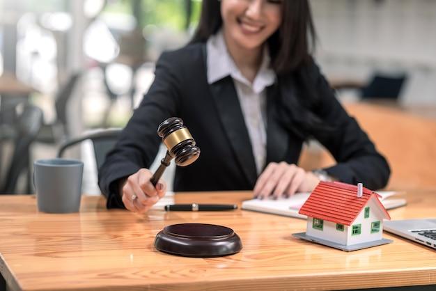 Крупный план женщины-юриста, держащей молоток с модельным домашним ноутбуком, помещенным в офис.