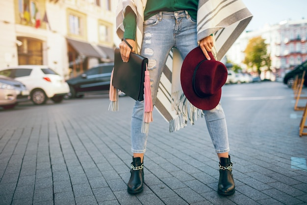 Крупным планом женские ноги в черных кожаных сапогах, джинсах, весенних тенденциях обуви, сумке