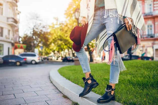 黒革のブーツ、ジーンズ、靴の春のトレンド、バッグを保持している女性の足のクローズアップ