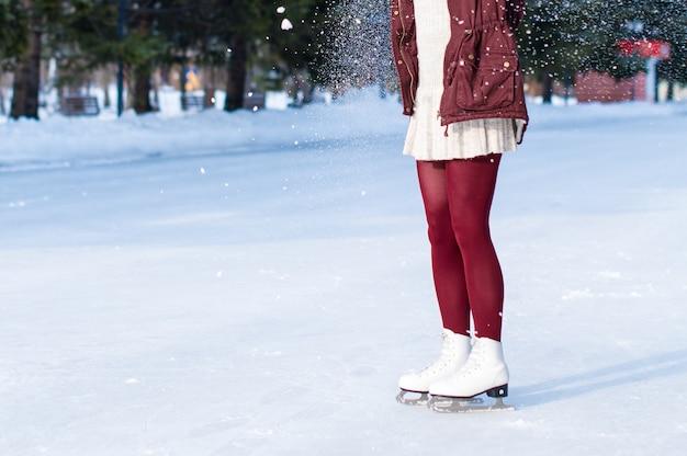 オープンスケートリンクで白い革のスケート靴を履いている女性の足のクローズアップ。テキストの場所