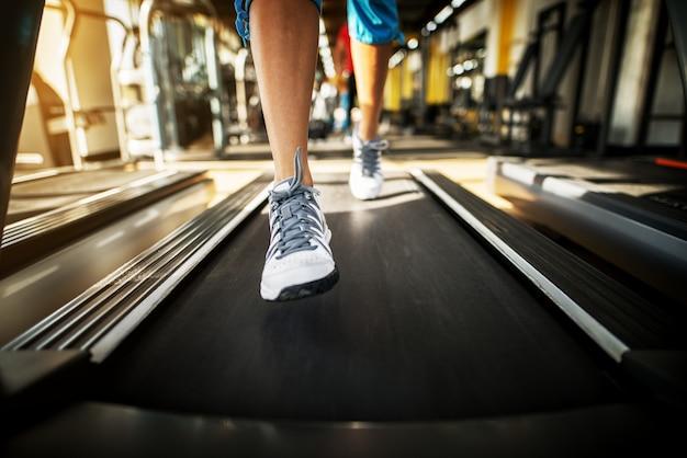 Закройте ноги женщины во время бега на беговой дорожке в солнечном тренажерном зале.