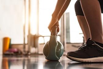 フィットネススポーツクラブのジムのトレーニングでダンベルのようなケトルベルを持ち上げる女性のクローズアップ