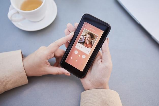 携帯電話に彼女の写真をロードし、オンラインでデートアプリを使用している女性のクローズアップ