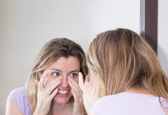 Close-up of woman looking at her face in the mirror