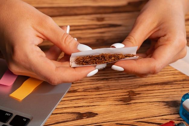 木製のテーブルで手巻きタバコを作る女性のクローズアップ