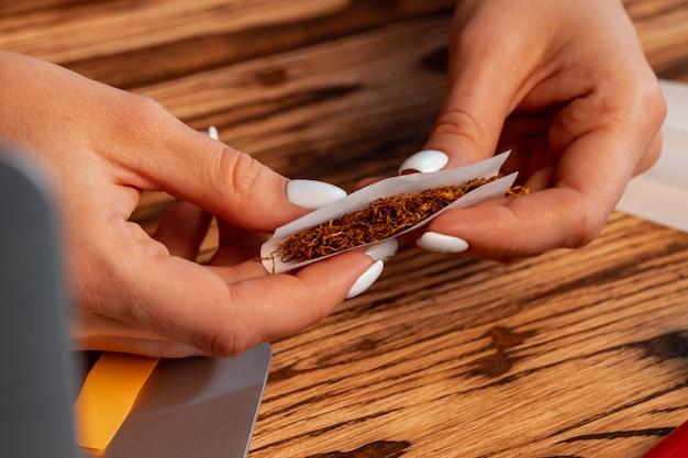 나무 테이블에 손으로 압 연 담배를 만드는 여자의 클로즈업