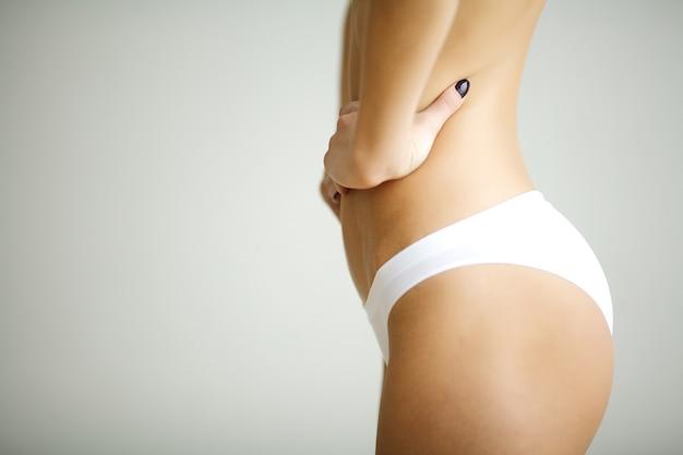胃に手を使ってハートの形を作る女性のクローズアップ